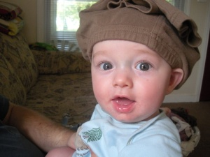 Baby with a pair of pants on his head.