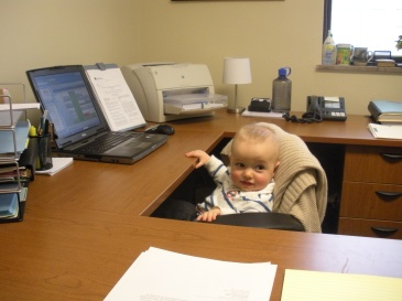 A baby sitting in an office chair